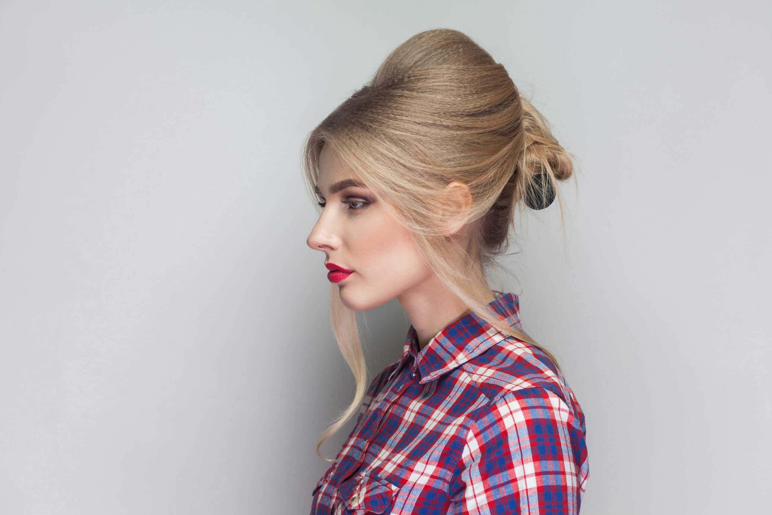 Profile side view of beautiful girl with pink checkered shirt, collected updo hairstyle, red lips and makeup standing with seious face and looking away. indoor studio shot, isolated on gray background