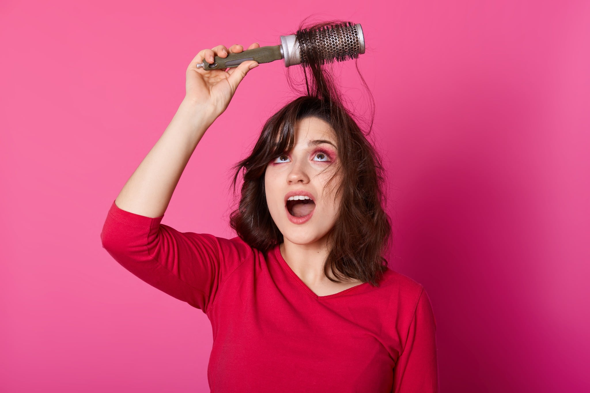 A woman on a pink background with her hair stuck in a round brush.