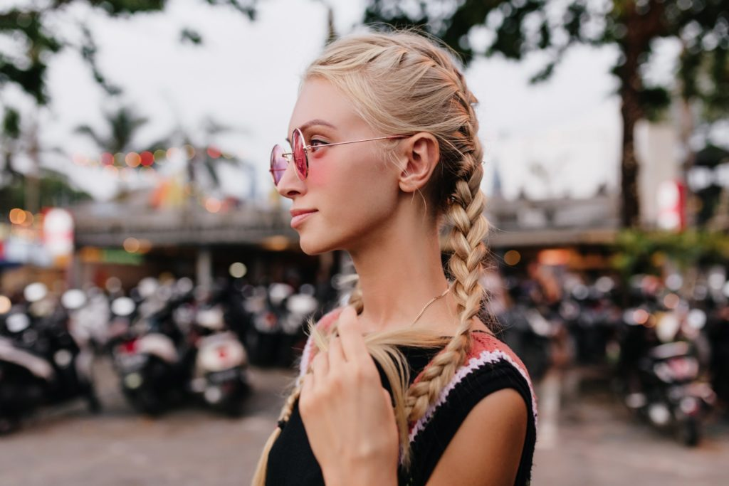 A blonde woman with french braid pigtails in her hair to prevent tangling.