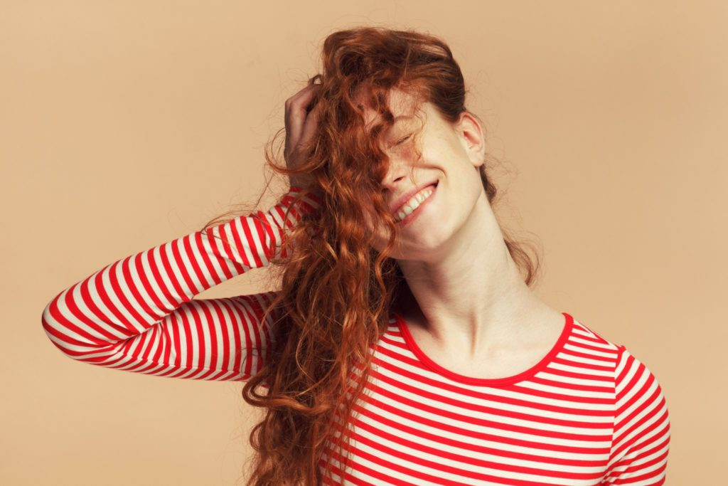 A girl with fine curly red hair smiling and touching her hair Spornette Professional Brushes