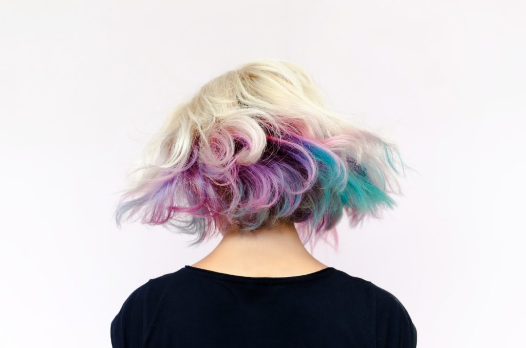 A woman flipping her brightly colored hair.
