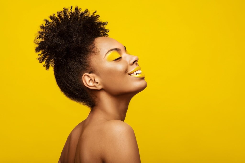 A woman wearing yellow makeup on a yellow background with a cute summer hairstyle Spornette Professional Brushes