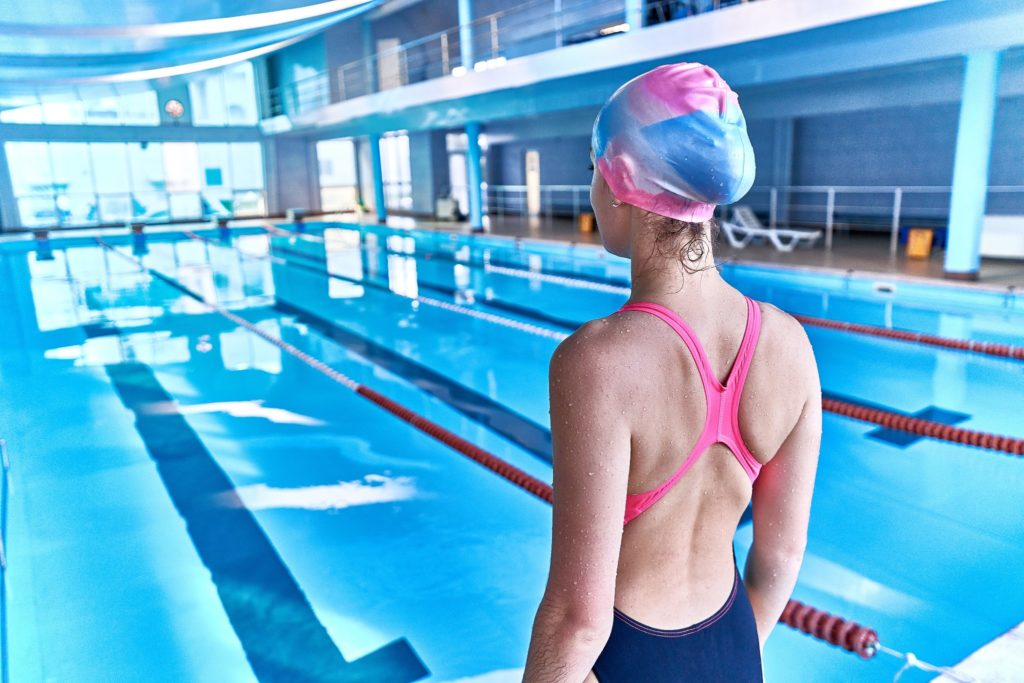A woman wearing a swim cap before swimming in a lap pool Spornette Professional Brushes